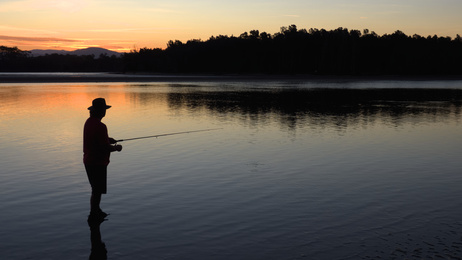 man fishing at sunset with nice reflections